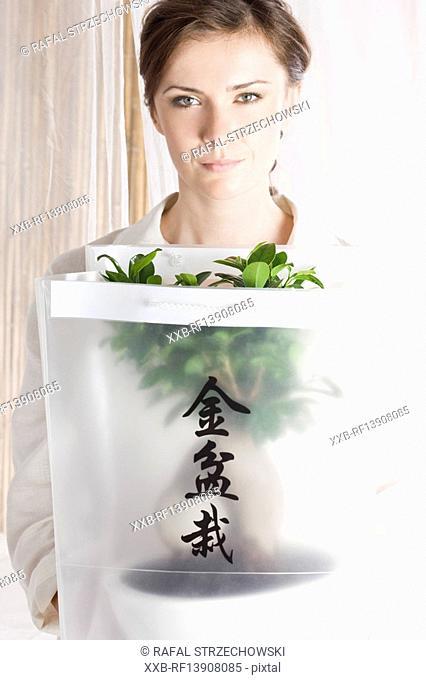 woman holding bonsai tree