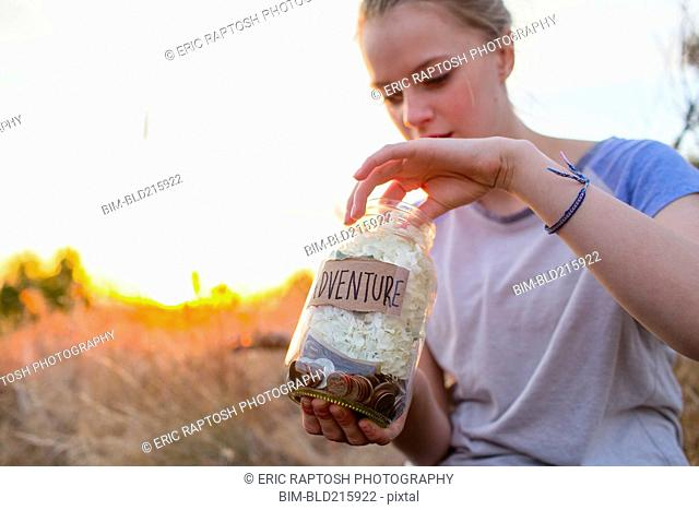 Caucasian teenage girl saving money in jar