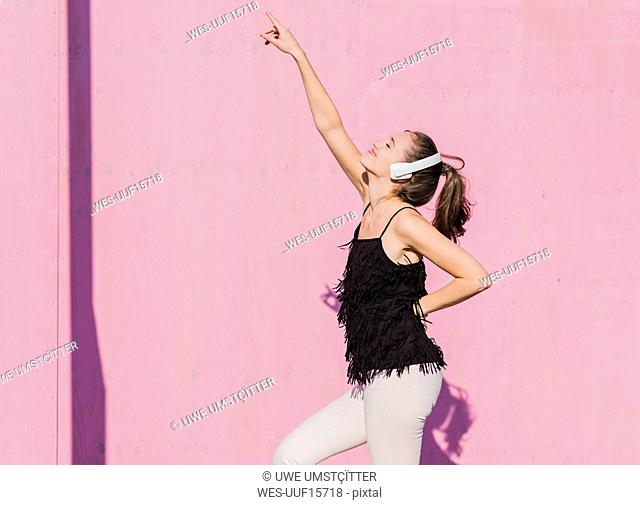 Happy young woman wearing headphones dancing in front of pink wall