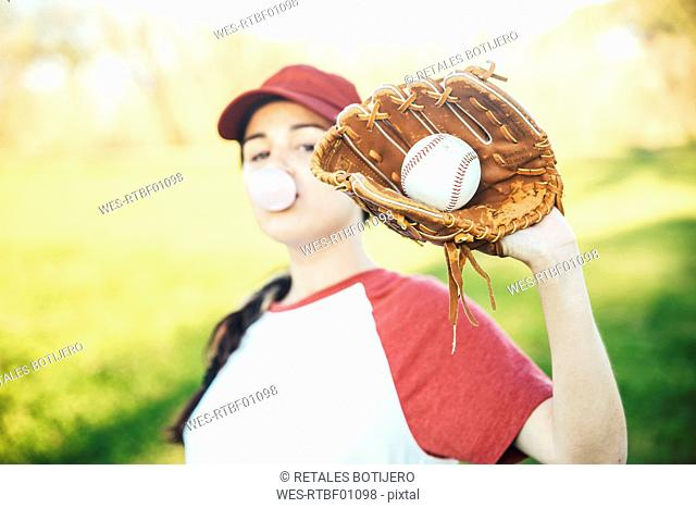 Portrait of young woman with ball and baseball glove blowing a gum bubble
