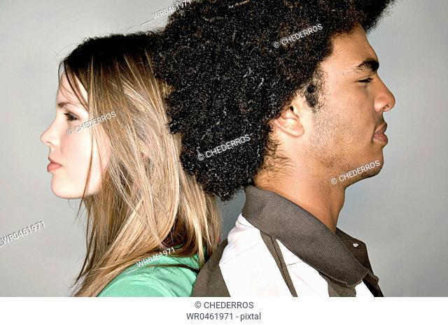 Side profile of a young couple back to back