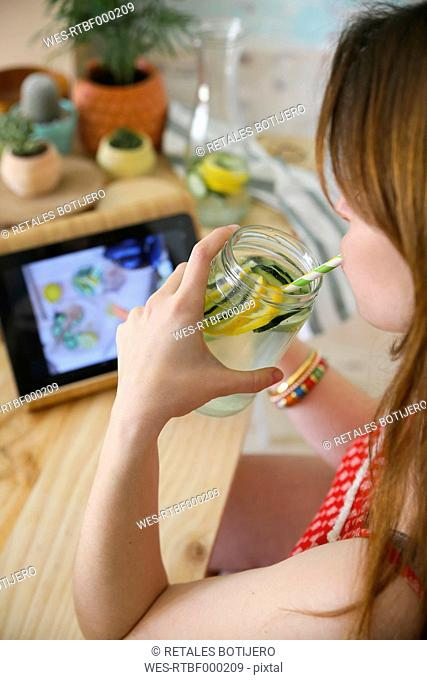 Woman drinking detox water infused with lemon and cucumber