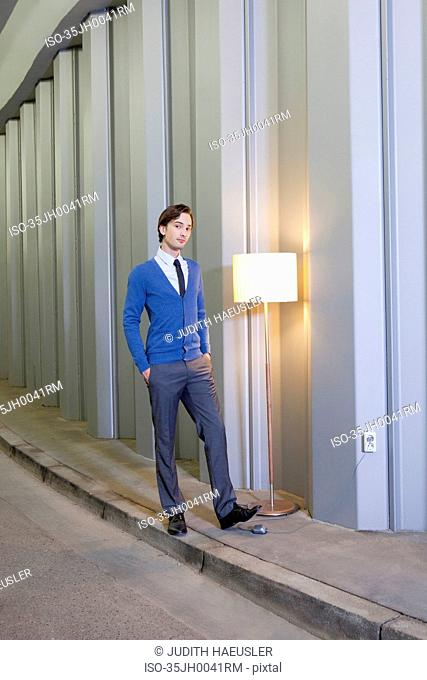 Businessman with lamp in empty hallway