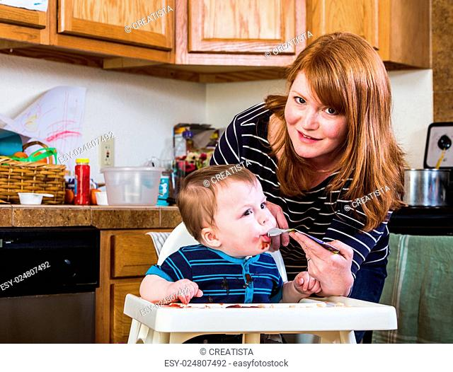 A woman feeds her baby juice in the kitchen
