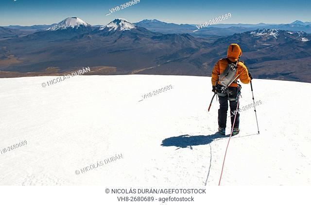 Climber on the summit of Sajama Volcano. The highest mountain in Bolivia (on the horizon Pomerape and Parinacota volcanoes) Sajama National Park