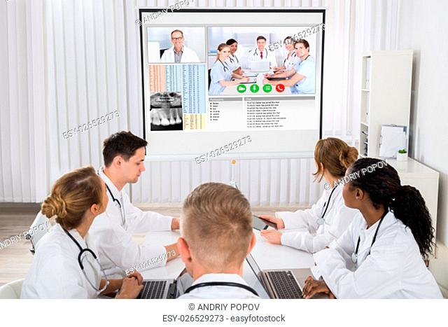 Group Of Doctors Videoconferencing With Male Doctor In Hospital