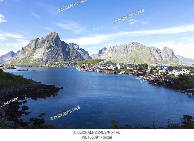 The blue sea frames the fishing village and the rocky peaks at dusk Reine Moskenes Lofoten Islands Norway Europe