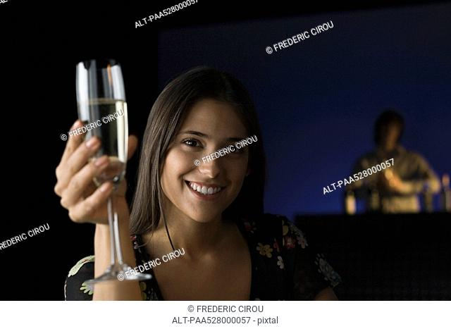 Woman holding up glass of champagne, smiling at camera, bartender in background