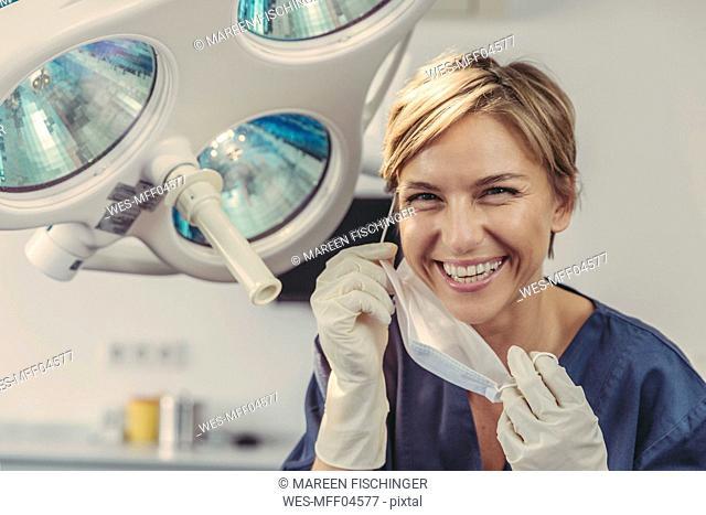 Dental surgeon removing surgical mask, portrait