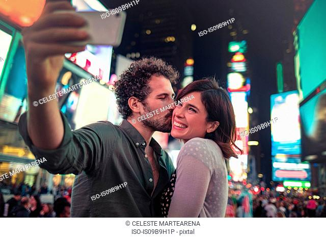 Couple taking selfie in Times Square, New York, United States, North America