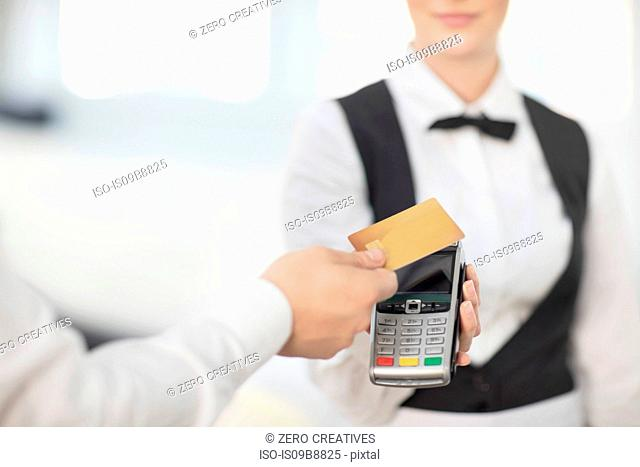 Waitress holding payment machine toward customer, customer paying by contactless method