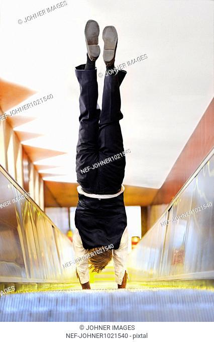 Man doing handstand on escalator
