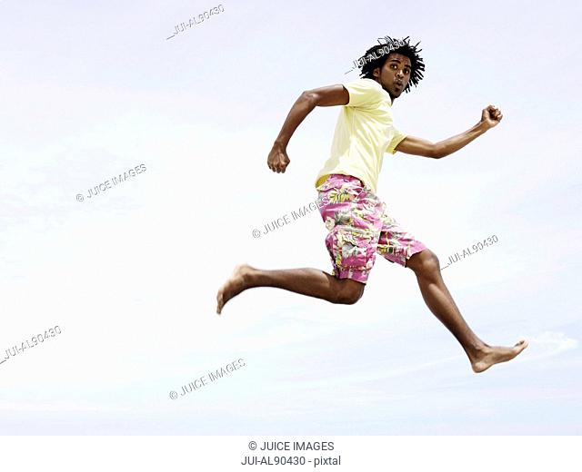 Low angle view of African man jumping