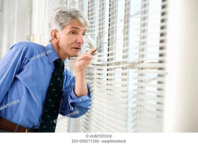 A business man looking out from his office window