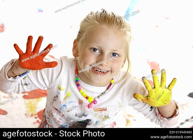 Child smiles and plays painter