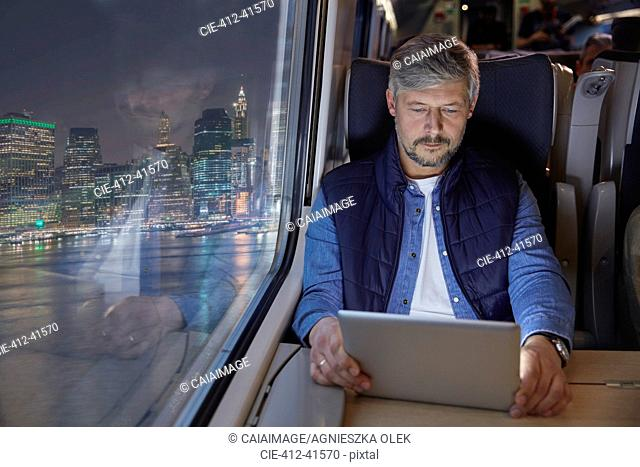 Man using digital tablet on passenger train at night