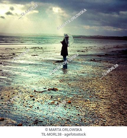 Young woman with umbrella standing alone on a stoney beach on a rainy day with dark clouds