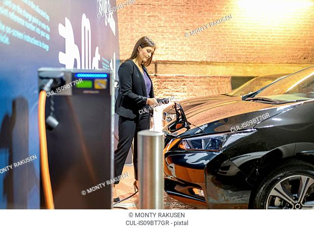 Businesswoman plugging in car at electric vehicle charging station, Manchester, UK