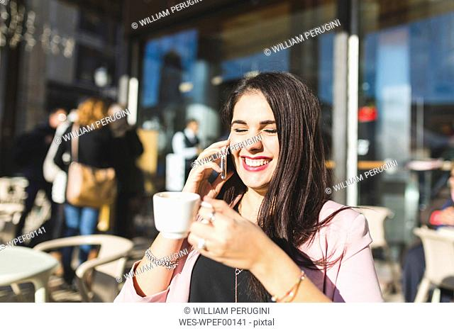 Laughing young businesswoman on cell phone at an outdoor cafe