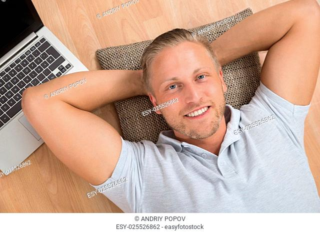 Young Happy Man Lying On Floor With Laptop