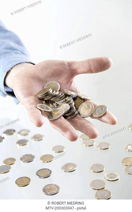 Businessman's open hand holding coins, Bavaria, Germany
