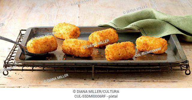 Potato croquettes on baking sheet on wire rack