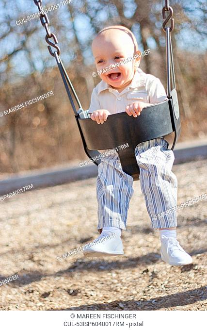 Baby boy playing on swing in park