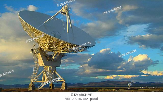 A satellite dish moves in time lapse against a beautiful sky