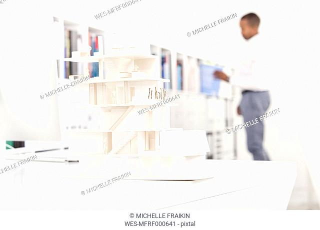 Architectural model on desk in an office with man in the background