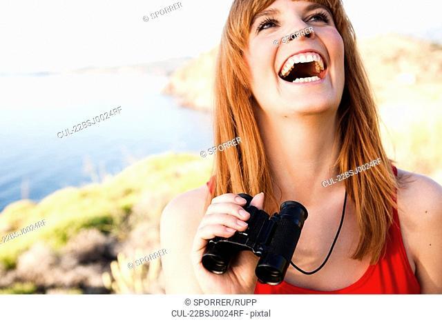 Woman with binoculars laughing