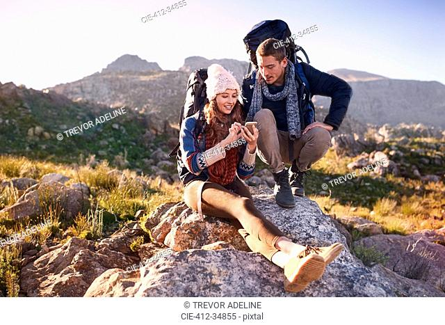 Young couple with backpacks hiking, resting on rock using smart phone