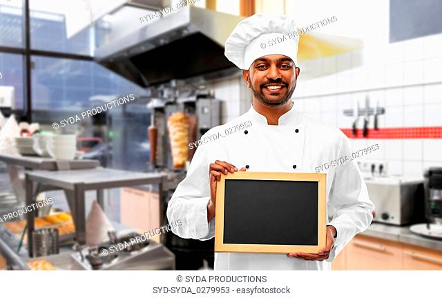 happy indian chef with chalkboard at kebab shop