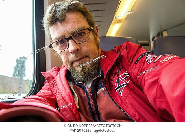 Zeeland, Netherlands. Self portrait of man in red jacket during a journey by train eastbound. Commuting by public transport is often cheaper than owning a car...