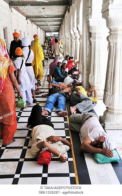 Inside the GoldenTemple complex under the sun is very hot People relaxing in the shade, Punjab Amritsar India