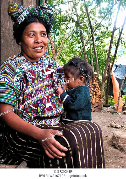Mayan woman in traditional clothing and nursing a child in a village close to Nebaj, Guatemala, Quiché, Nebaj