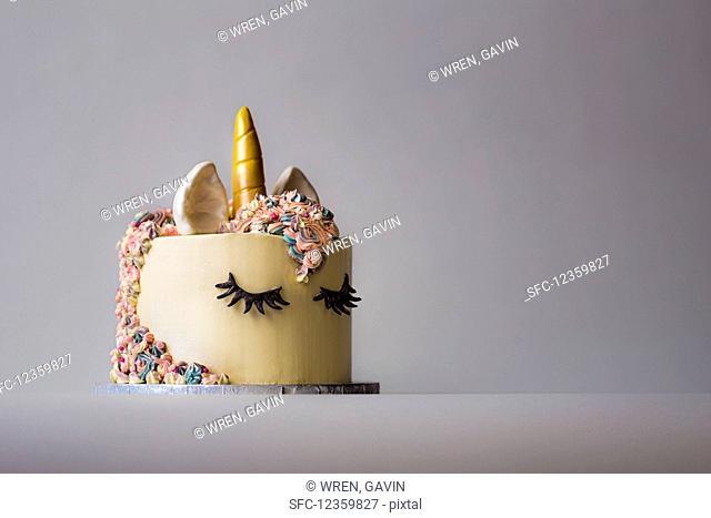 A bespoke made unicorn celebration cake made with multocoloured mane and golden horn