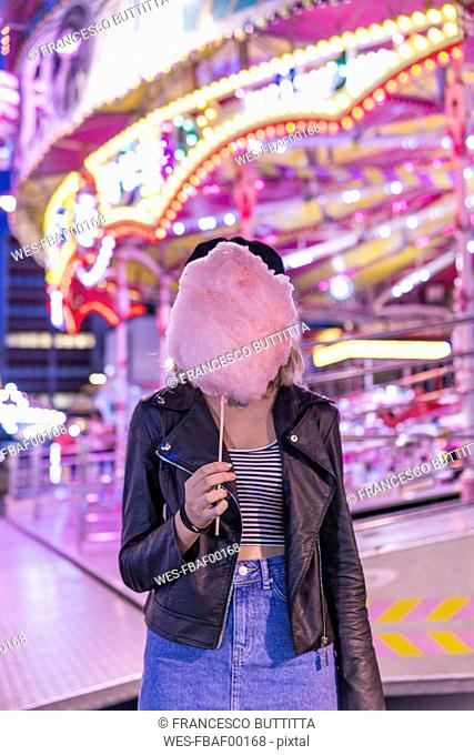 Teenage girl hiding her face behind pink candyfloss at fair