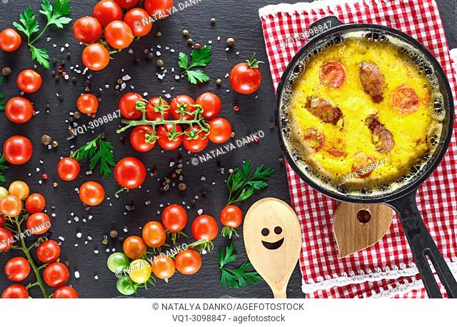 black round frying pan with fried omelette, whipped eggs with cherry tomatoes, top view