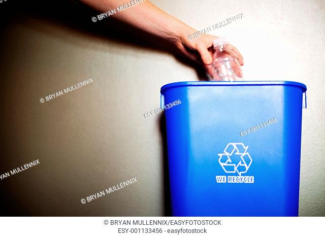 Woman's arm dropping plastic bottling into recycling container