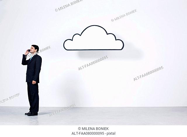Businessman talking on cell phone near graphic cloud representing cloud computing