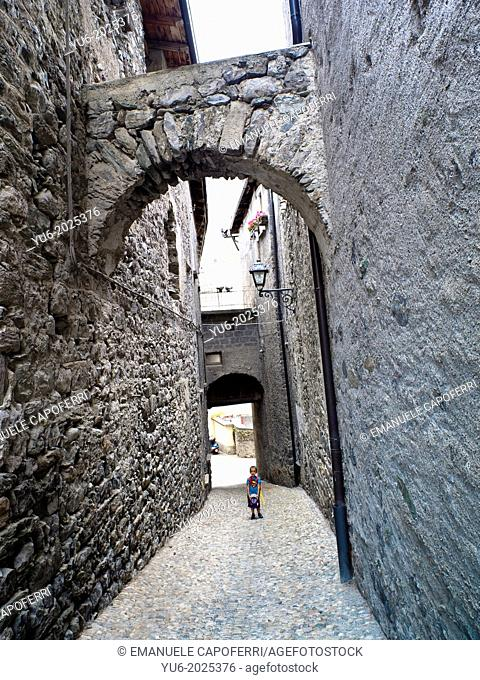 Child in an ancient street of the medieval town of Bormio, Sondrio, Italy