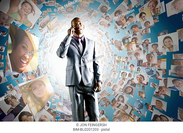 African American businessman on cell phone in front of images of business people