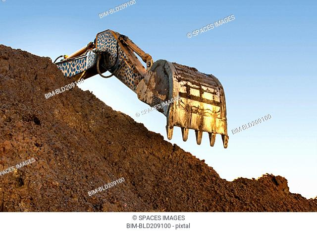 Earth mover scoop over heap of dirt in quarry