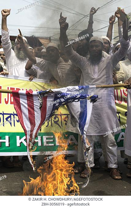 DHAKA, BANGLADESH - MAY 18 : Bangladeshi muslims burn flags of Israel and the U. S. in a protest against recent violence in Palestine