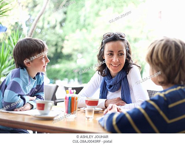 Woman at cafe with two boys