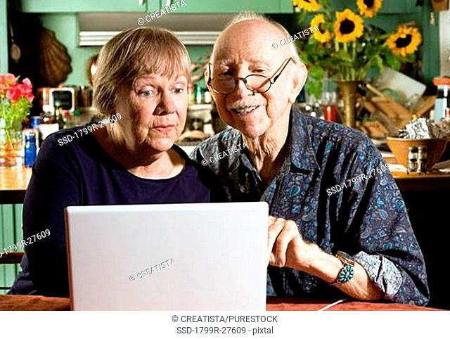 Senior couple with a laptop in a dining room