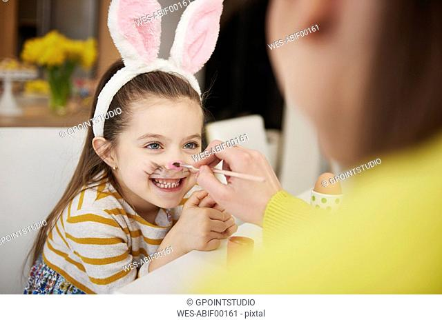 Mother painting daughter's face wearing bunny ears