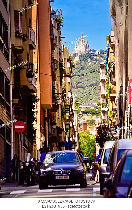 Car in a street. At the bottom, Collserola mountain and Tibidabo with the popular church. Barcelona, Catalonia, Spain