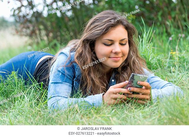 Cool longhaired teenage girl is lying on the grass and viewing her smart phone