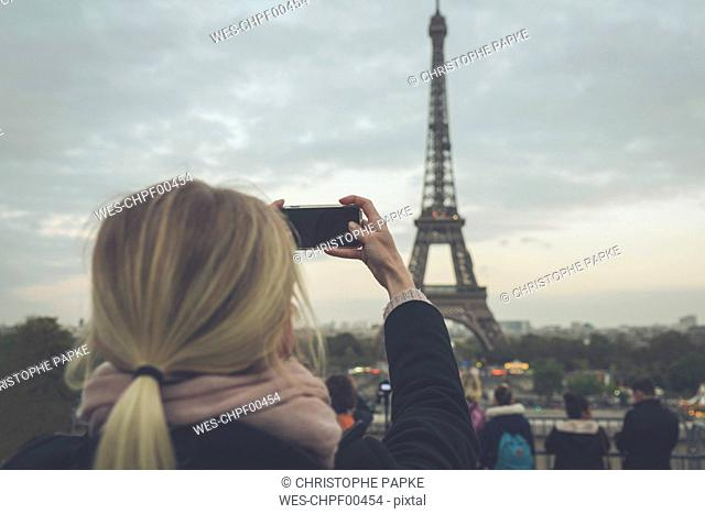 France, Paris, Eiffel Tower, woman photographing with smartphone